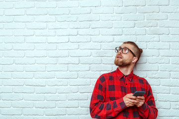 Young Handsome Man Using Mobile Phone While Leaning on Brick Wall