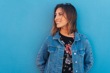 Portrait of happy young woman leaning on blue wall