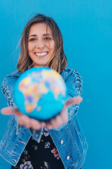 Pretty young woman offering world globe in hands