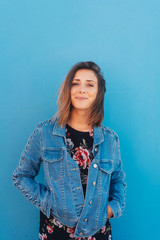 Smiling pretty woman on blue wall background