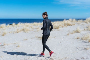 Fit young woman jogging on a sandy beach