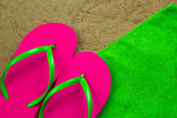 top view slippers  a green towel on a bech