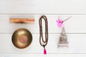 Meditation or mindfulness concept. Wooden mala beads, tibetan singing Bowl with symbol OM  and Buddha statue with flower on wooden background with copy space.