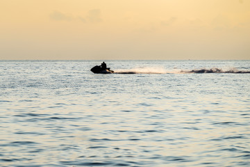 Silhouettes of people in motion on jetski