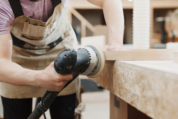 Carpenter polishes the wooden surface of furniture products. Electric eccentric orbital grinding machine. Mechanized woodworking carpenter hand tool in working carpentry workshop.