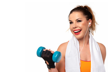 Fitness activity concept - beautiful young woman in sportswear with towel, earphones and dumbbells making workout (copy space)