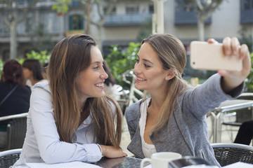 Happy friends making selfie. Two beautiful young women making selfie on urban background