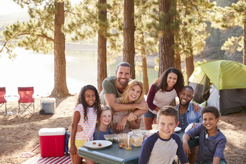 Portrait Of Family With Friends Camping By Lake In Forest