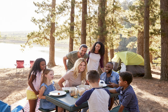Family With Friends Camp By Lake On Hiking Adventure In Forest