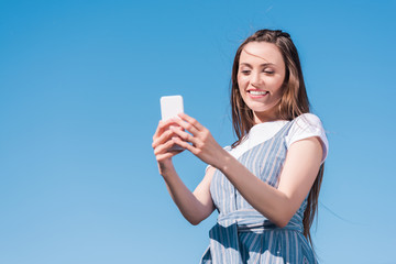 attractive young woman taking selfie on smartphone against blue sky