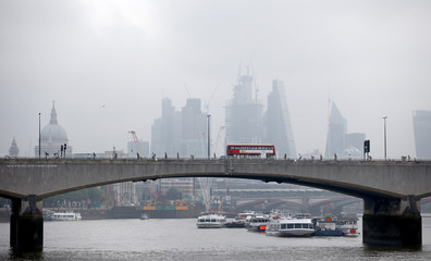 A traditional red London bus crosses Waterloo Bridge, with the financial district in the background, in London
