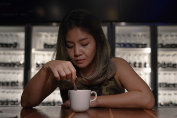 Asian woman holding teaspoon and white cup of coffee