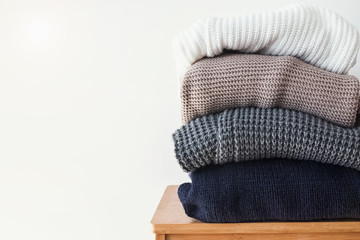 Wall Mural - Stack of cozy winter sweaters on the white wall background.