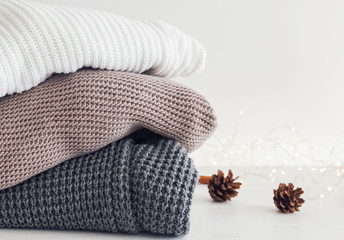 Wall Mural - Warm knitted sweaters and pine cones on the background.