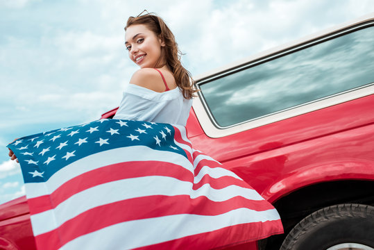 attractive girl with american flag standing near red car