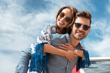 handsome man in sunglasses piggybacking his smiling girlfriend