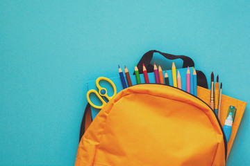 Back to school concept. Backpack with school supplies. Top view. Copy space. Toned