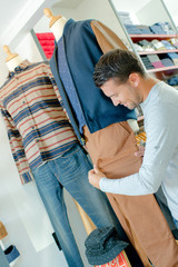 Man looking at width of trouser leg on mannequin