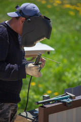 Welder welds metal at the construction site