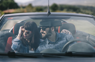 Man and woman travel in convertible car.