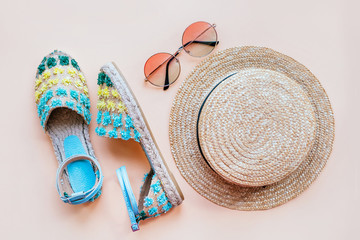 Summer fashion flatlay with espadrille sandals, gradient round sunglasses and straw hat on the beige background. Perfect beach set for holidays on the sea. Marina style.
