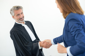 Legal worker in robes shaking hands with woman in suit