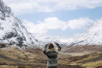 Happy Girl in knitted wool sweather dancing and enjoying a mountain view in Glen Coe, Scotland