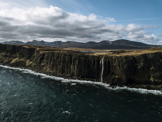 Waterfall falling into the Atlantic Ocean on the Isle of Skye, Scotland during a cloudy sunny day