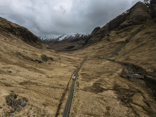 Aerial perspective of a mountain valley with road and river and caravan camper in Glen Coe, Scotland during a moody day