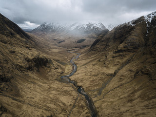Aerial perspective of a mountain valley with road and river in Glen Coe, Scotland on a moody day