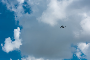 Drone flying high with blue cloudy sky in the background.