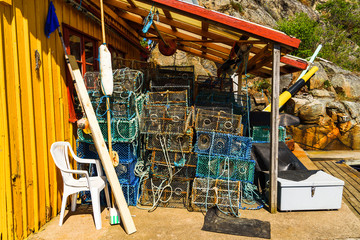 Lots of crab or lobster traps under a roof beside a shed.