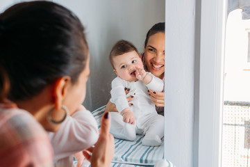 Cheerful woman holding baby near mirror