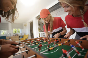 Girls having fun playing foosball at home