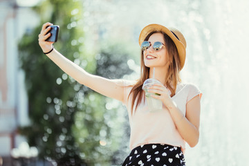 Youngpretty girl take selfie from hands with phone on summer city street. Urban life concept.