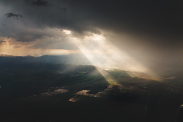 Dramatic aerial view of storm clouds with light ray and sun beam