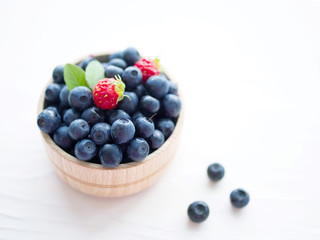 Fresh blueberries in a cup on a wooden surface. Closeup.
