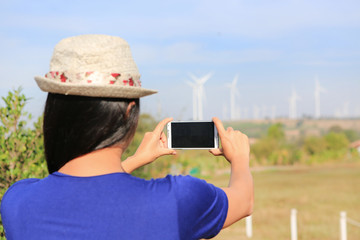 Back view of young Asian woman taking photo with smartphone of wind turbine field.