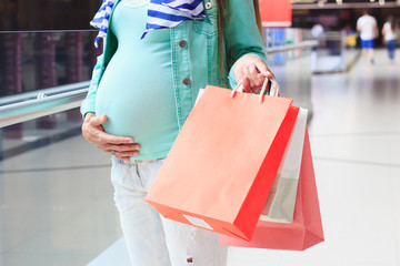 Beautiful pregnant woman with paper packages in the mall