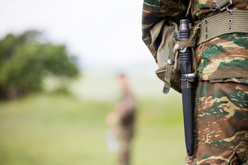 Soldier' body with camo clothing and knife in his belt. Close up behind view, blurred soldier and nature background, copyspace.