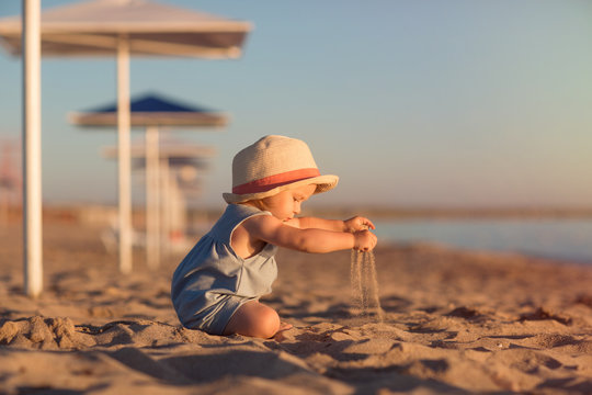 kid in a hat playing with sand on the beach by the sea. holidays with children near the ocean