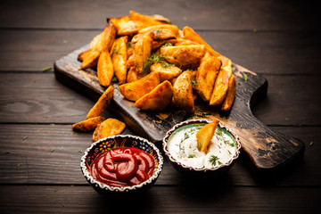 Baked potato fries on wooden table