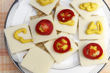 Red Jalapenos, Cheddar Cheese, Mustard on Crackers. Snack of crackers with red jalapenos, cheese and mustard. Appetizer of cheese mustard pepper slices.