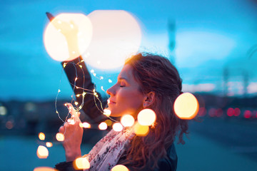 Woman holding fairy light garland at evening and dreaming outdoors