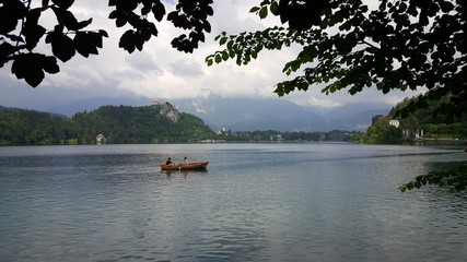 Couple floating at Bled island and Alpine lake, Slovenia