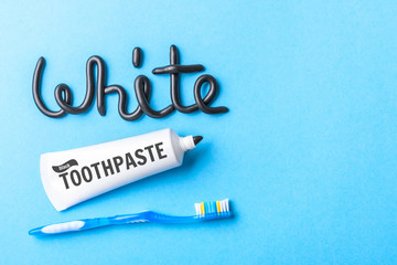 Black toothpaste from charcoal for white teeth. Word WHITE from  black toothpaste,  tube and toothbrush on  blue background. Copy space for text