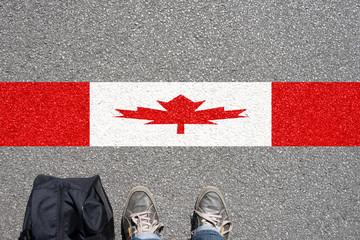 Ein Mann mit dem Koffer steht an der Grenze zu Kanade