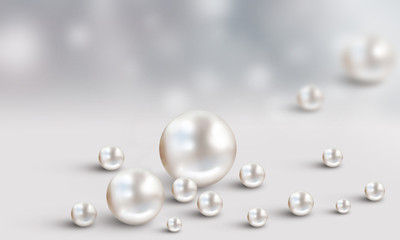Many scattered white pearls on grey and white cloudy blur background