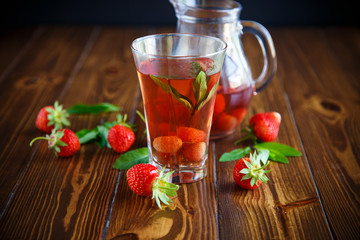 Sweet compote of ripe red strawberries in a glass decanter