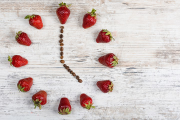 strawberry clock with arrows from coffee beans, showing a time of five or seventeen hours on a wooden vintage background